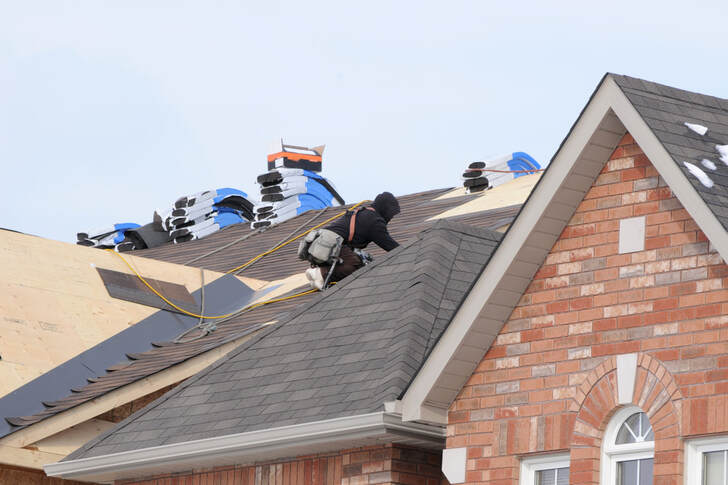 roofers installing new shingles
